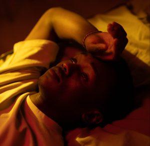 Die Abbildung zeigt einen jungen Mann, der auf seinem Rücken in einem Bett liegt. Sein rechter Arm liegt angewinkelt neben seinem Kopf und seine Hand auf seiner Stirn. Er guckt nach oben und sein Blick wirkt nachdenklich und traurig. Das Bild ist insgesamt dunkel und viele Schatten sind zu sehen.